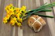 Hot cross bun and daffodils. - 49910930