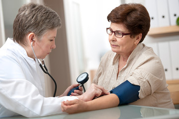doctor measuring blood pressure of female patient