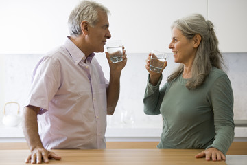 Mature couple drinking glasses of water
