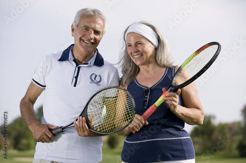 Mature couple holding tennis racquets