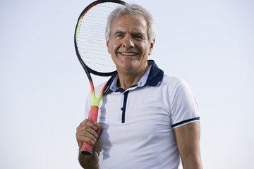 Mature man holding tennis racquet