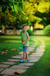 little boy in a green shirt walking along the paths in the park