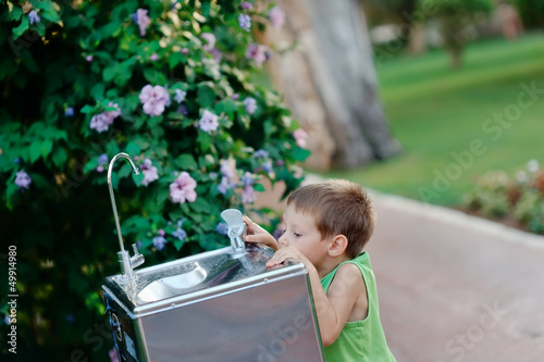 little boy reaching for the tap water in the street to get a dri