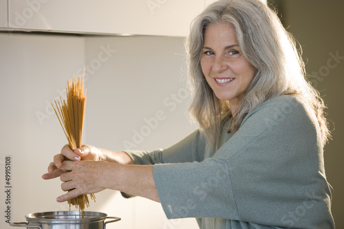 Mature woman cooking spaghetti