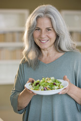 Mature woman holding bowl of salad