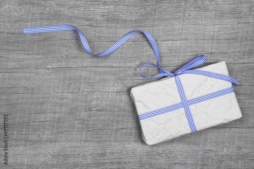 Geschenk in Blau auf Holz Hintergrund