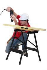 Handyman drilling a piece of wood.