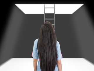 woman standing in a pit looking up to the ladder that leads out