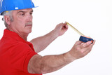 Middle-aged handyman using tape-measure