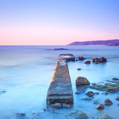 Concrete pier or jetty and rocks on a blue sea. Hills on backgro © stevanzz