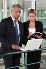 businessman and businesswoman verifying data