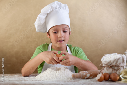 Little chef preparing the dough for cookies