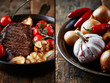 Steak with grilled garlic, chili peppers, onions and tomatoes