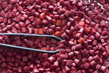 Red plastic masterbatch granules with a tweezers