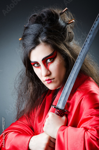 Female sword warriod in dark studio