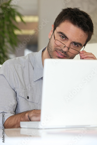 Man with glasses in front of computer