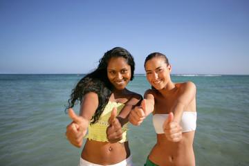 two girlfriends having fun on the beach