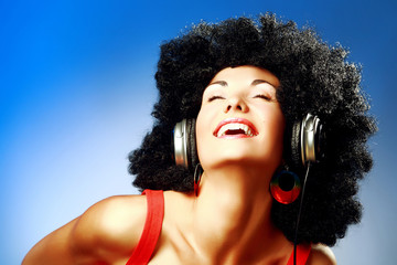 Happy woman with afro haircut enjoying music in headphones