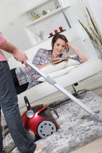 Husband vacuuming whilst wife lays on sofa