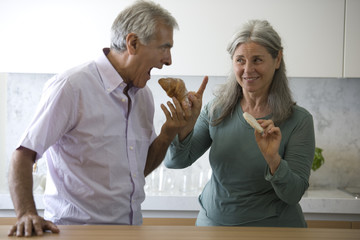 Mature couple eating snack food