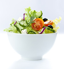 Greek salad with feta in a white bowl