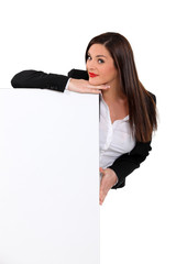 Brunette woman behind white panel