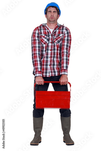 Worker trying to carry heavy toolbox