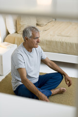 Mature man doing yoga in bedroom