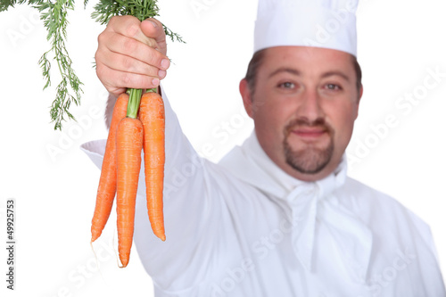 chef holding a bunch of carrots