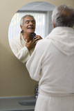 Mature man shaving in bathroom mirror