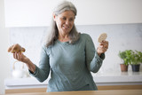 Mature woman deciding between croissant and rice cake
