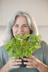 Mature woman holding basel plant