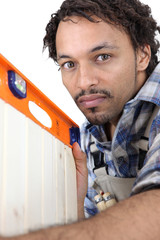 Man using spirit-level to check cabinet door