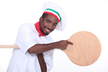 Pizza maker pointing to a pizza peel