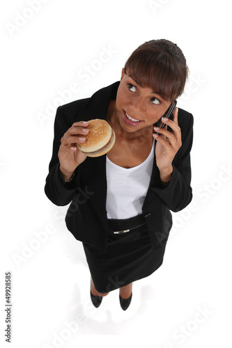 businesswoman eating a hamburger and talking on her cell