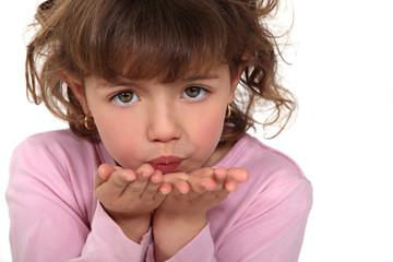 little girl sending a kiss