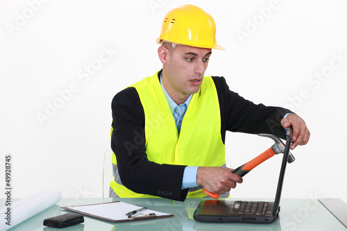 Builder smashing laptop screen with hammer