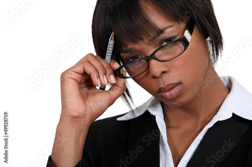 Stern businesswoman touching her glasses