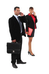 businessman and businesswoman talking on their cells