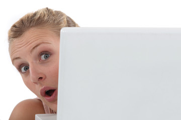 Woman with laptop in state of surprise