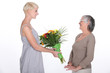Young woman offering a bouquet of flowers to her grandmother