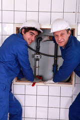 Plumber with young apprentice