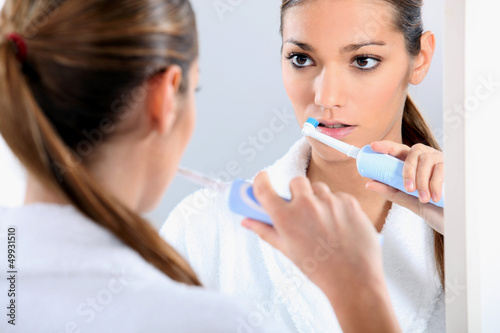 Woman with an electric toothbrush