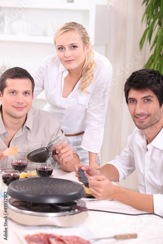 Three friends eating a raclette