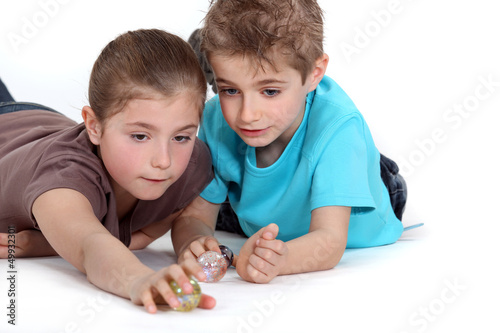 Brother and sister playing with marbles