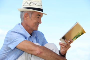 A mature man reading a book outside.