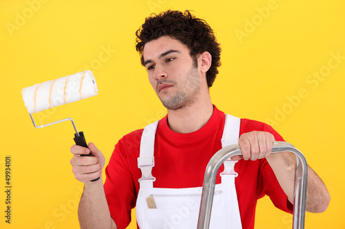 Man on step-ladder holding paint roller