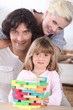 Couple playing a stacking game with their daughter