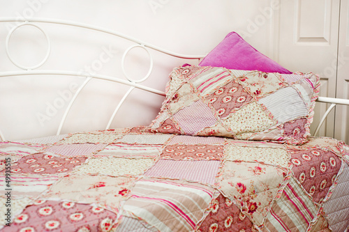 pink patchwork quilt on a bed