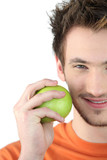 Young man holding a green apple